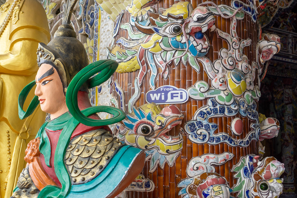 Free WiFi Sign next to Dragons and Ornaments inside a Pagoda in Da Lat, Vietnam