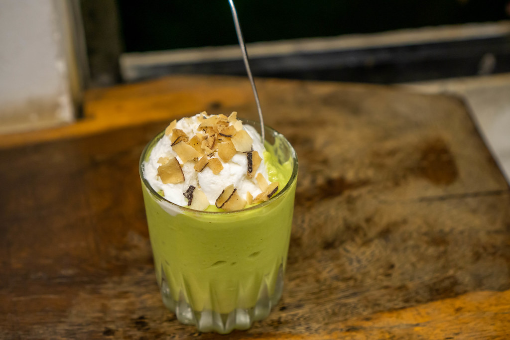 Avocado Coconut Ice Cream with Almond Flakes in a Glass with Spoon