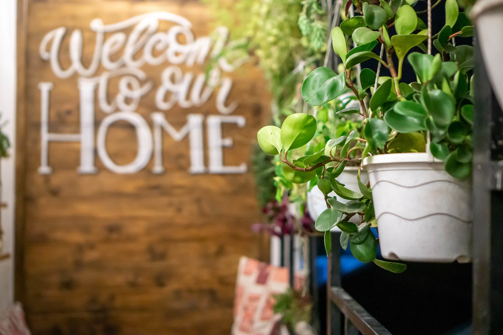 Hanging Plant Pots on a Balcony with Words Welcome to our Home on a Wooden Wall