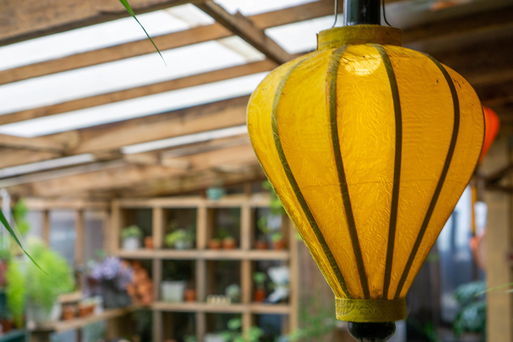Close Up Photo of Yellow Hanging Lantern inside a Cafe with Wooden Design