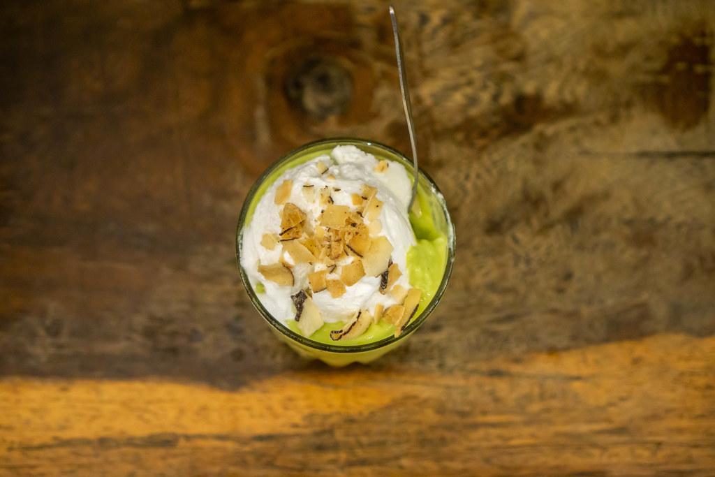 Avocado Kokosnuss Eiscreme mit Mandelblättchen im Glas mit Löffel von oben fotografiert