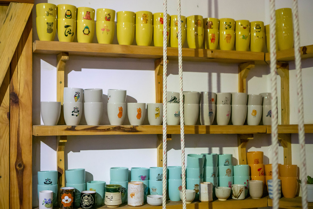 Ceramic Cups in different Colors displayed on a Wooden Shelf inside a Cafe