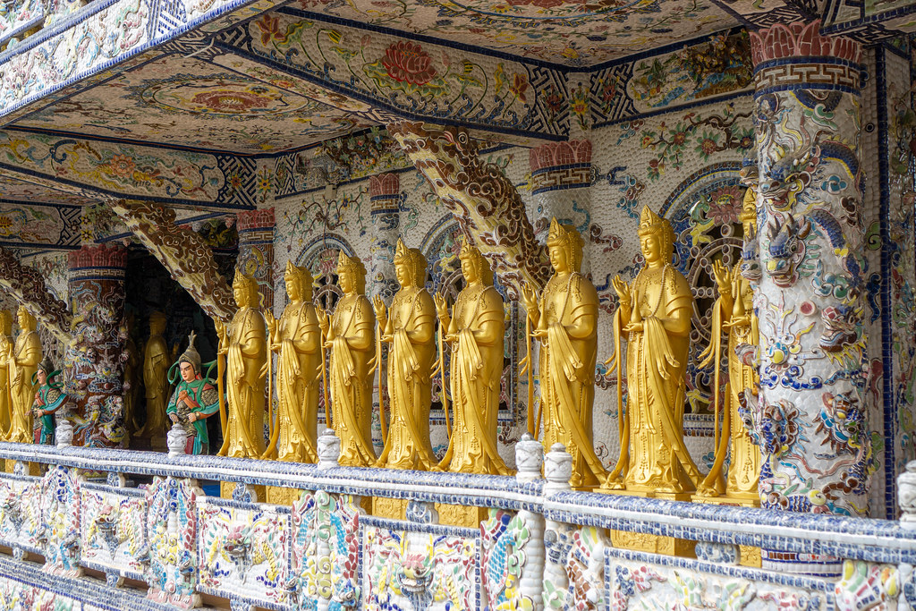 Many Golden Lady Buddha Statues in front of a Mosaic Wall at Linh Phuoc Pagoda in Da Lat, Vietnam