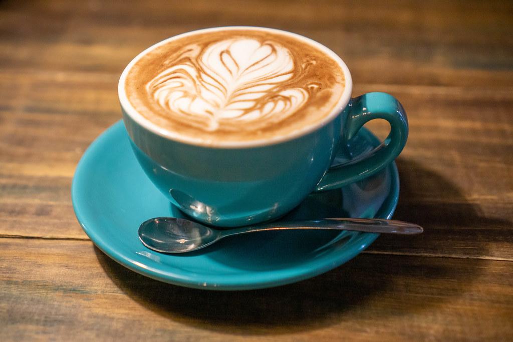 Cappuccino in Keramiktasse mit Löffel und Untertasse auf Holztisch Nahaufnahme