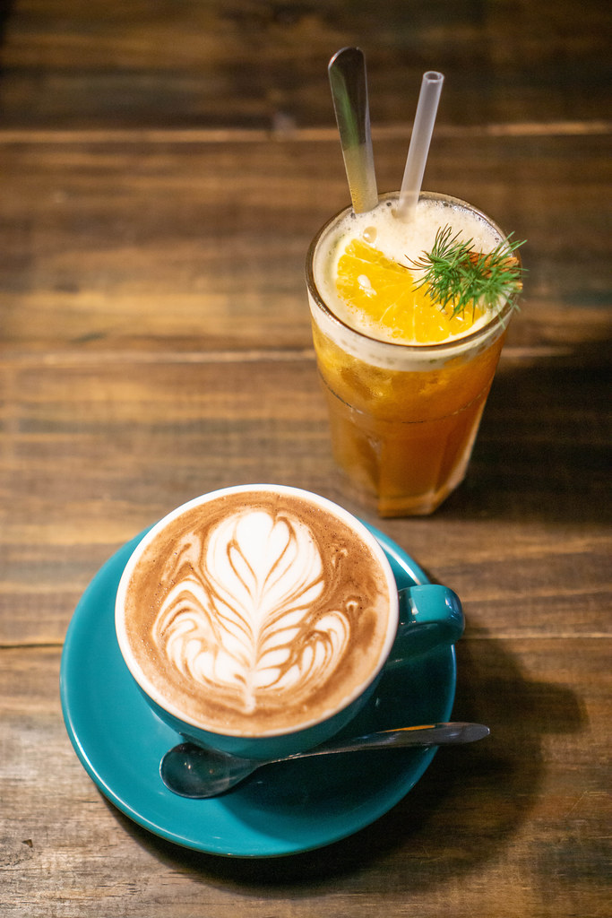 Top View Food Photo of Orange Cinnamon Tea and Cappuccino on a Wooden Table