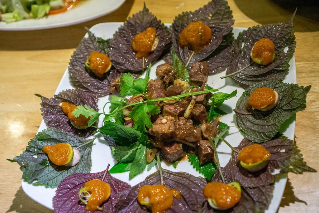 Vietnamesisches Gericht mit gebratenem Rindfleisch, Kräutern und Kumquat Sauce von oben fotografier