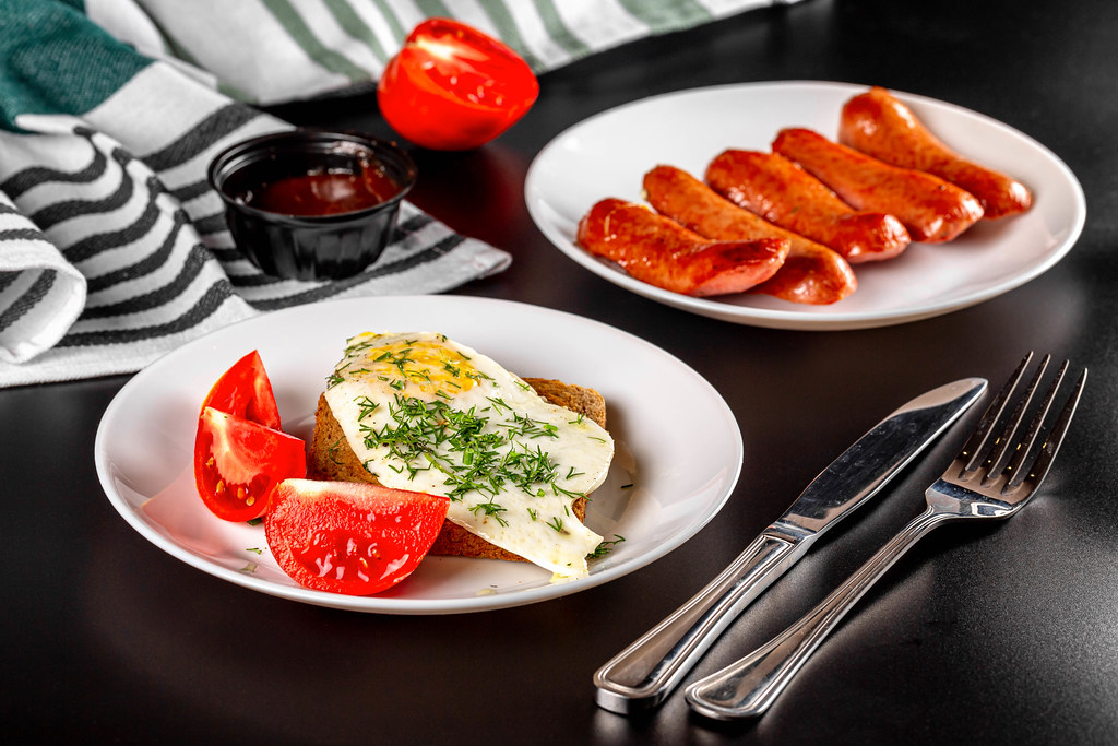 Breakfast background with fried eggs, sausages, bread and sliced tomato