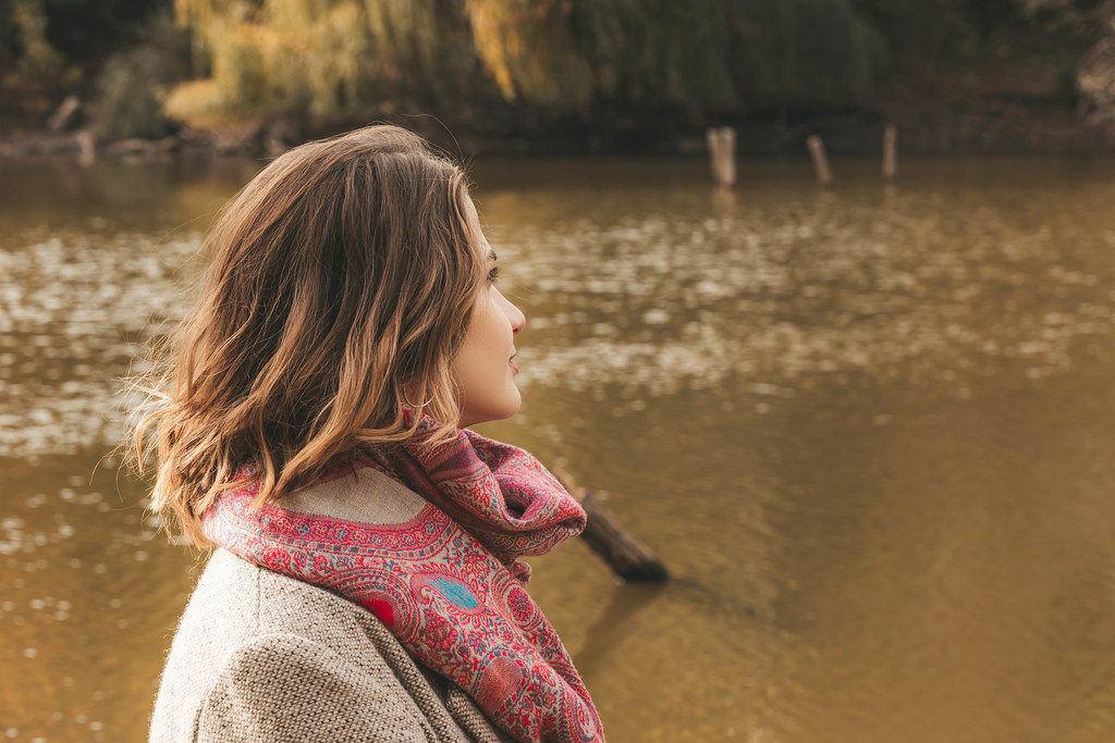 Girl looks at the lake, beautiful autumn landscape