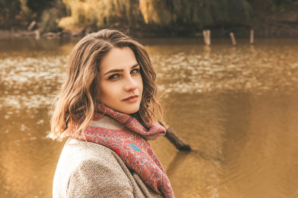 Portrait of a young woman on the background of a pond