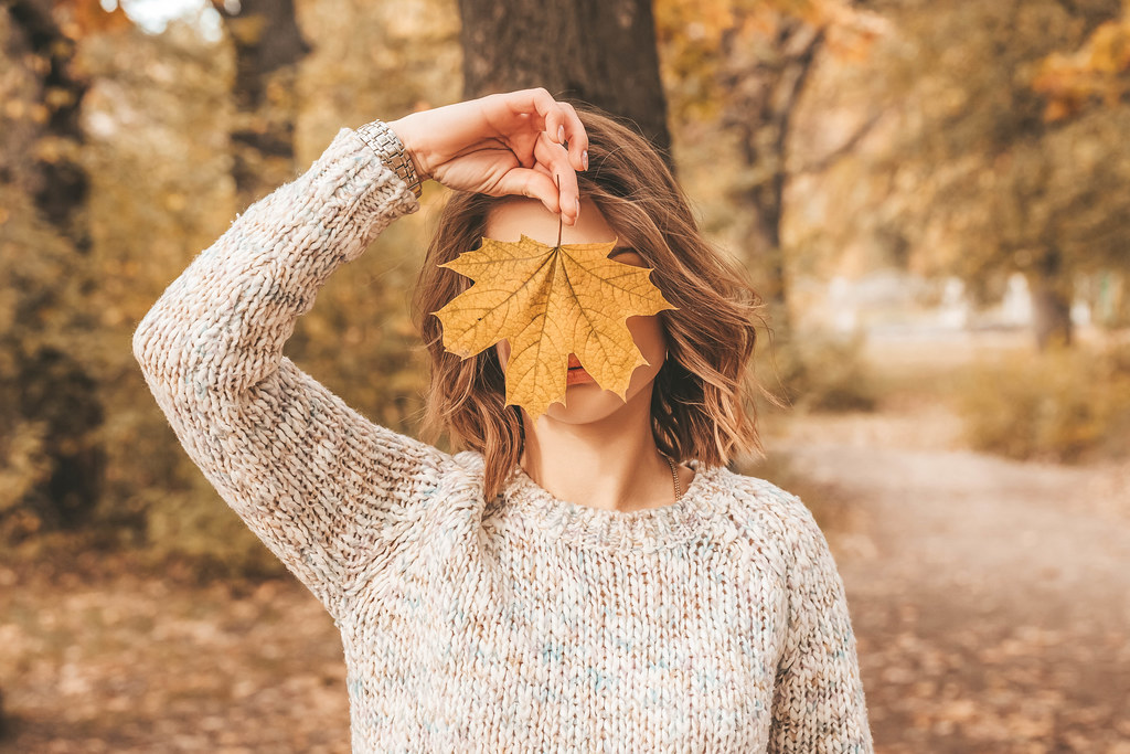 Autumn portrait girl covers her face with maple leaf