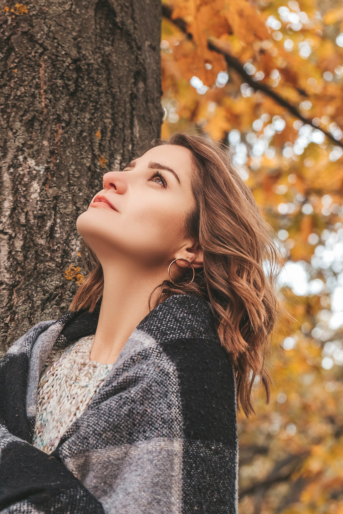 Beautiful girl resting in the park in autumn