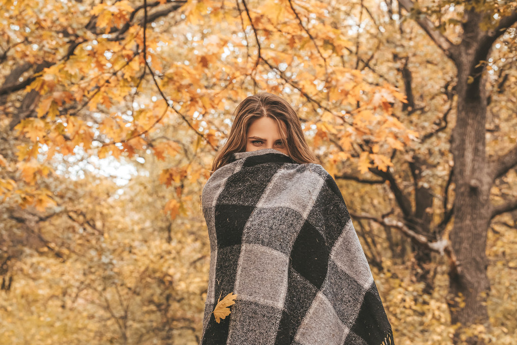 Young woman walking in autumnal park, hiding her face with warm woolen plaid
