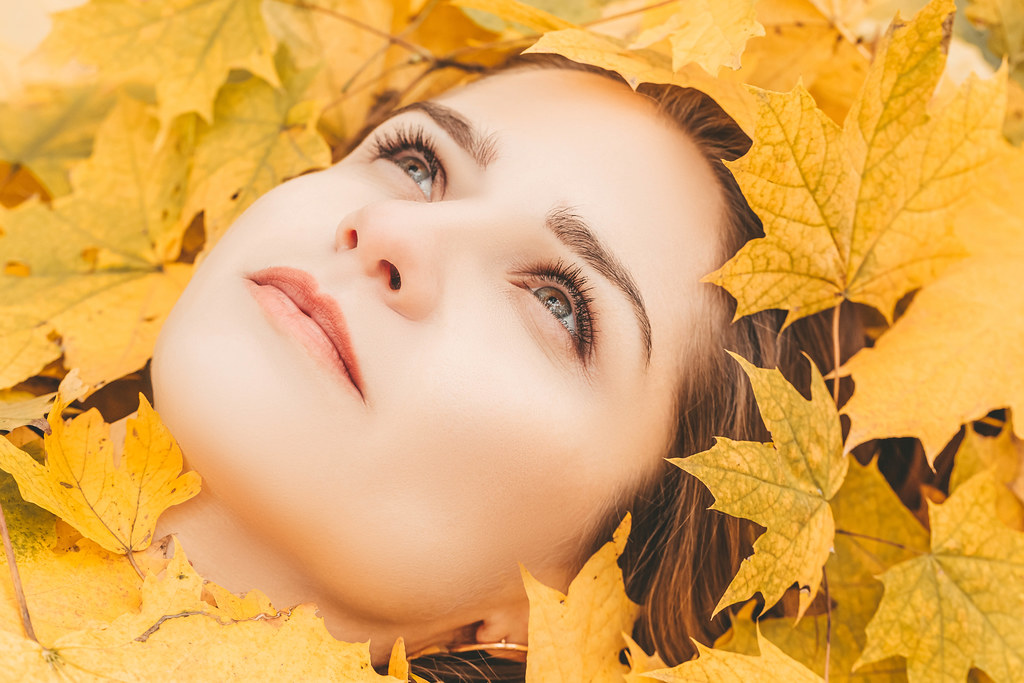 Autumn woman portrait. Beauty model girl with autumnal yellow leaves