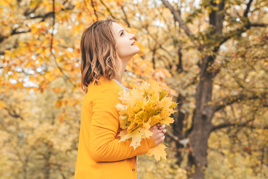 A girl looks at an autumn Park with leaves in her hands