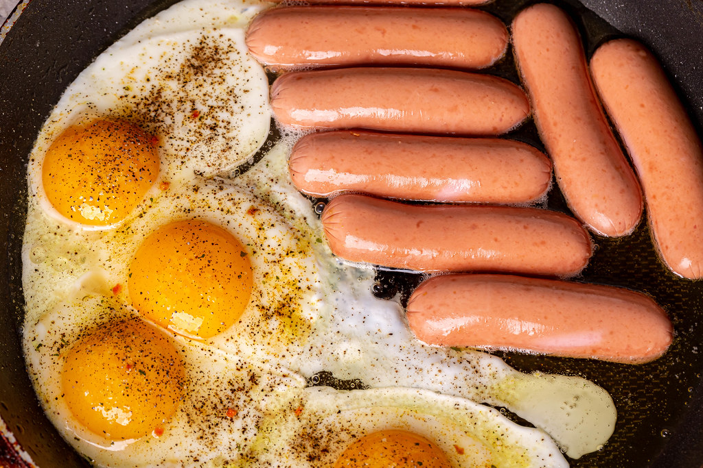 Frying pan with fried eggs and sausages, breakfast cooking concept