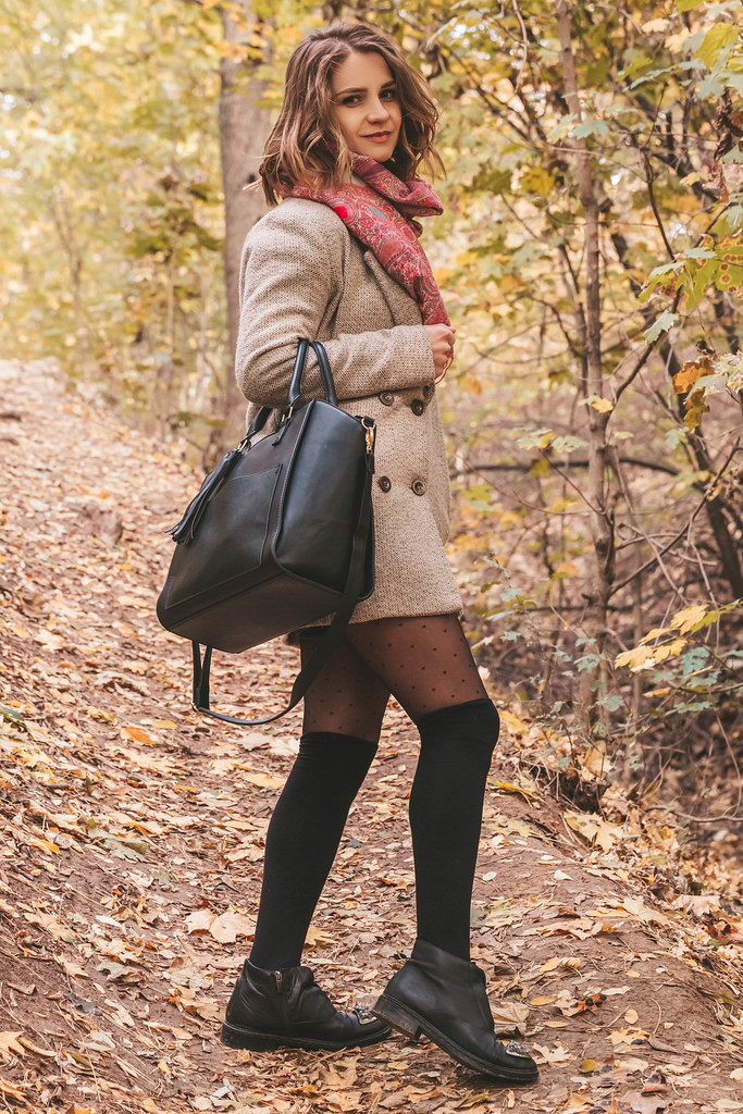 Girl walks with a handbag in the autumn forest