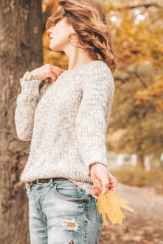Woman in knitted sweater on autumn background