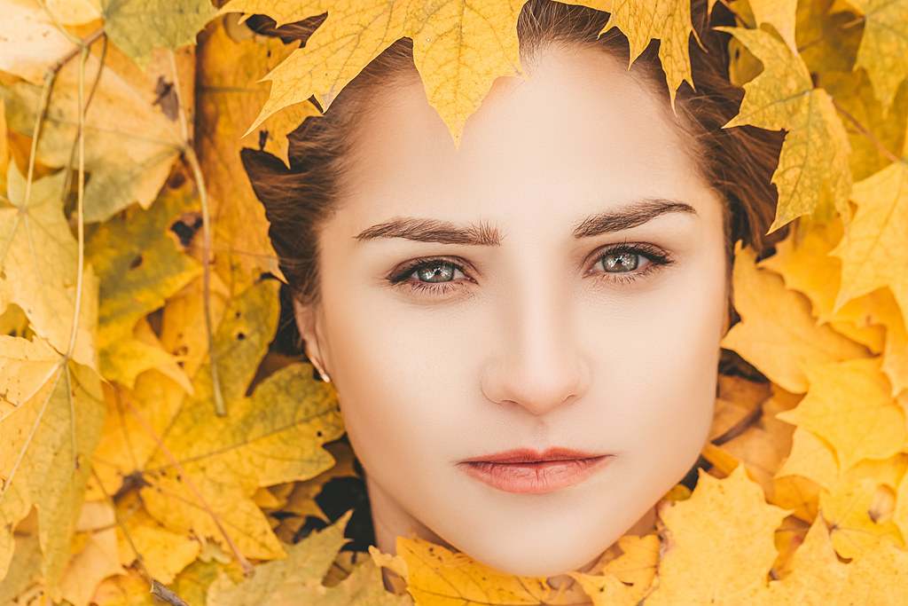 Close-up of a girl's face surrounded by yellow maple leaves