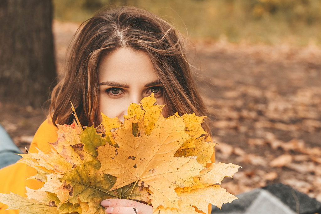 Close-up of a girl's face and yellow leaves