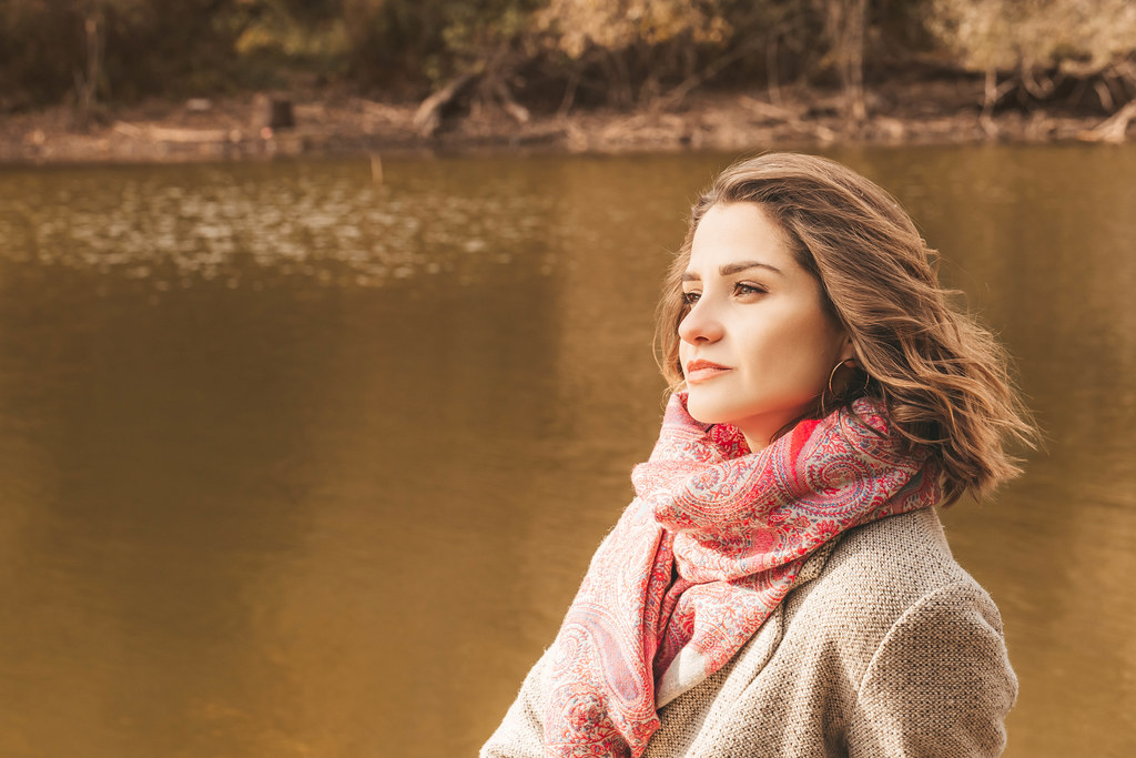 Beautiful pensive girl near the autumn pond