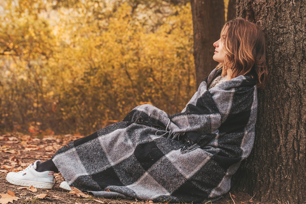 Pretty woman wrapped herself in a blanket and sits under a tree