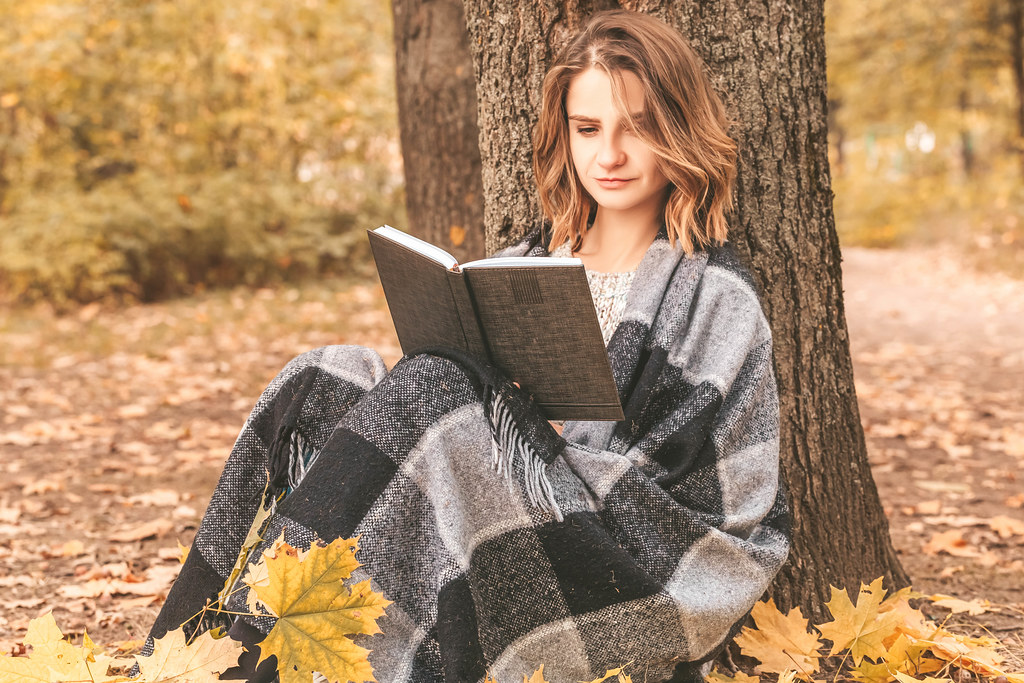 Beautiful young girl sitting on a fallen autumn leaves in a park, reading a book