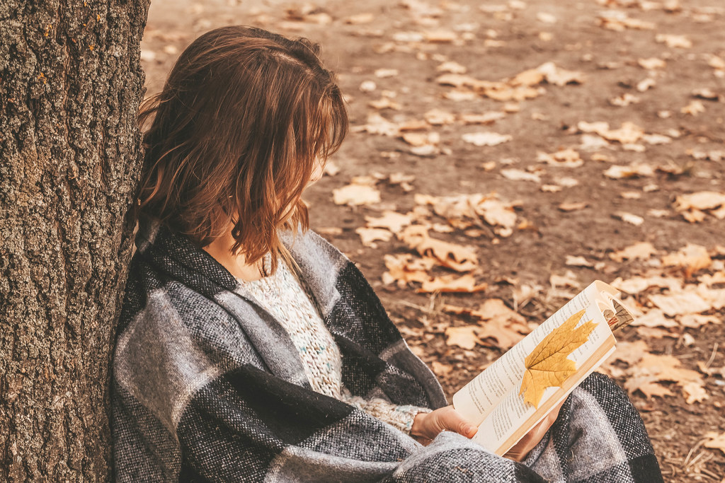 Woman sitting in the forest and reading a book, autumn rest