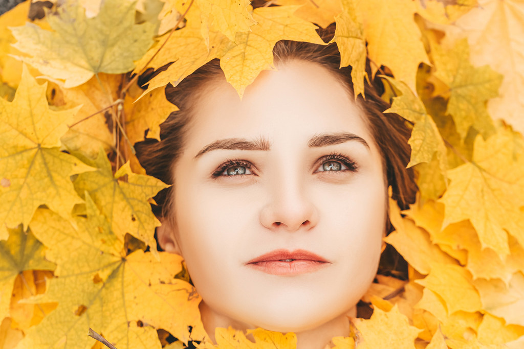 Beautiful elegant woman portrait with autumn leaves