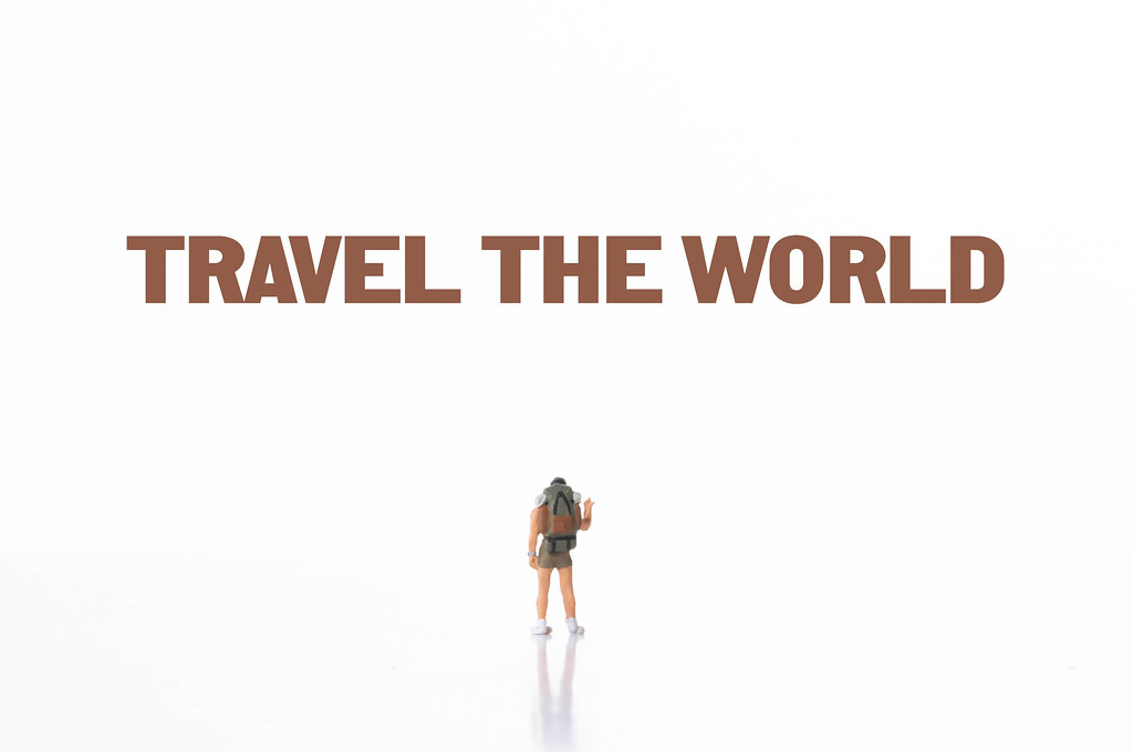 Small traveler with Travel The World text