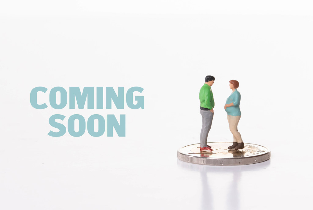 Pregnant woman and man standing on 2 Euro coin with Coming Soon text