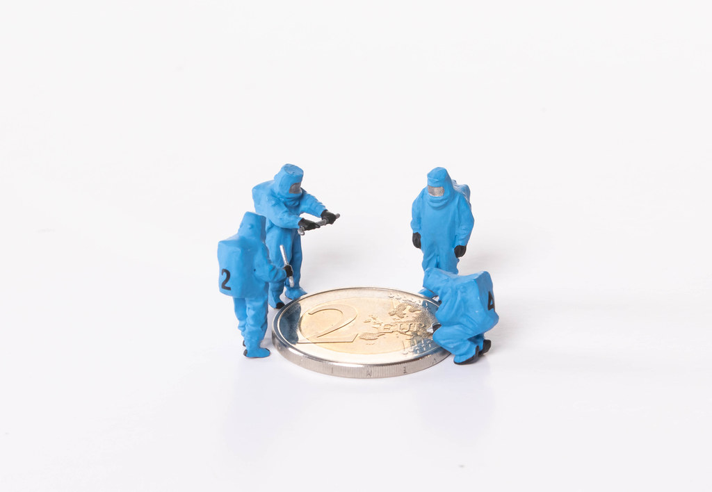 Workes in blue protective suits standing around 2 Euro coin