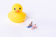 Couple in bathing suit with yellow rubber duck on white background