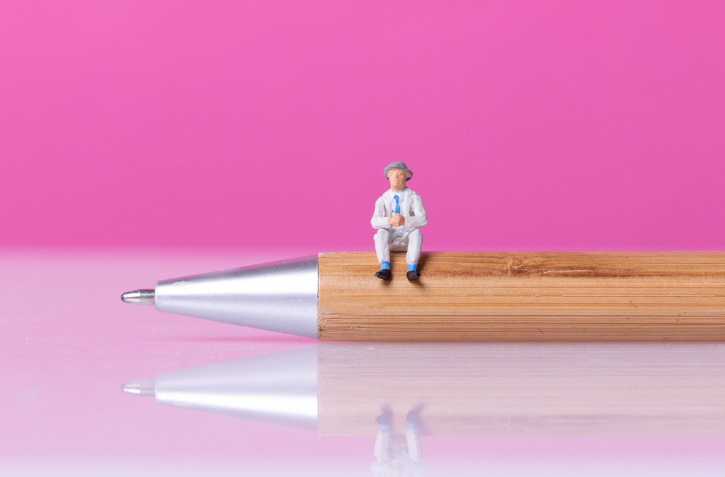 Man sitting on a wooden pen with pink bakground