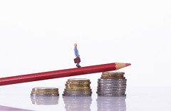 Man walking on a red pencil laying on a stack of coins