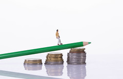 Man walking on a green pencil laying on a stack of coins