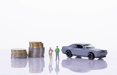 Couple with coin stacks and sports car on white background