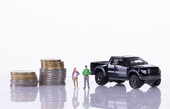 Couple with coin stacks and pickup truck on white background