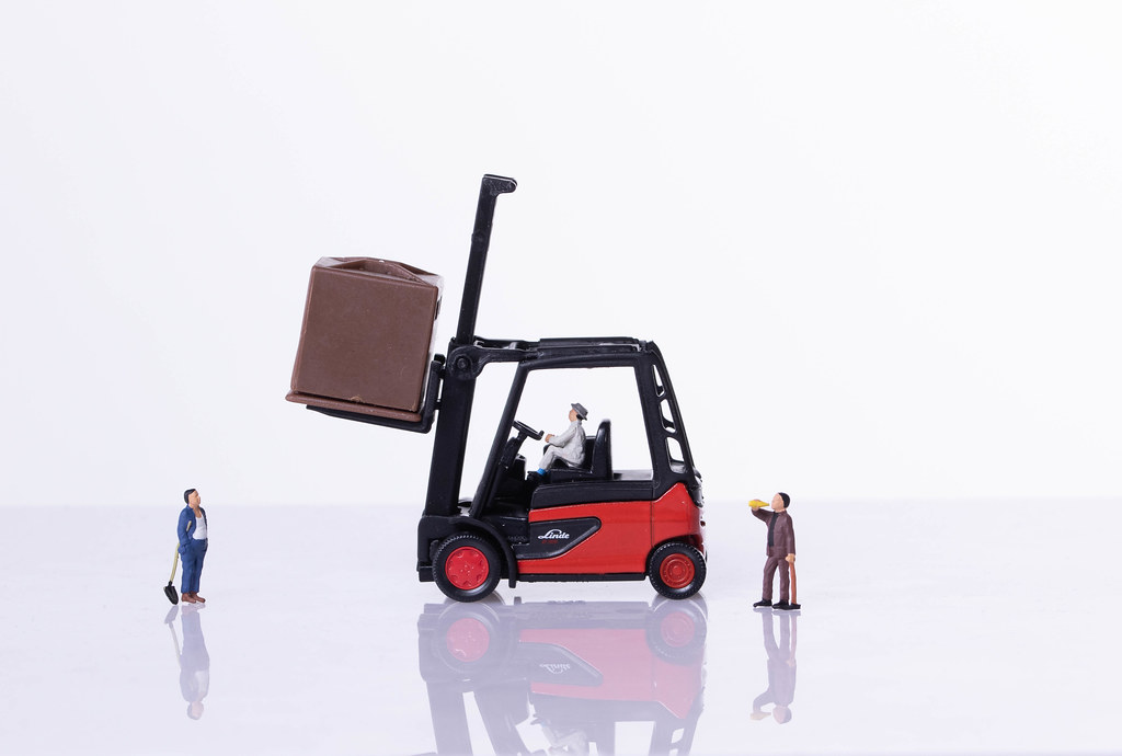 Red forklift with miniature workers on white background