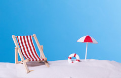 Beach chair with beach umbrella on blue background