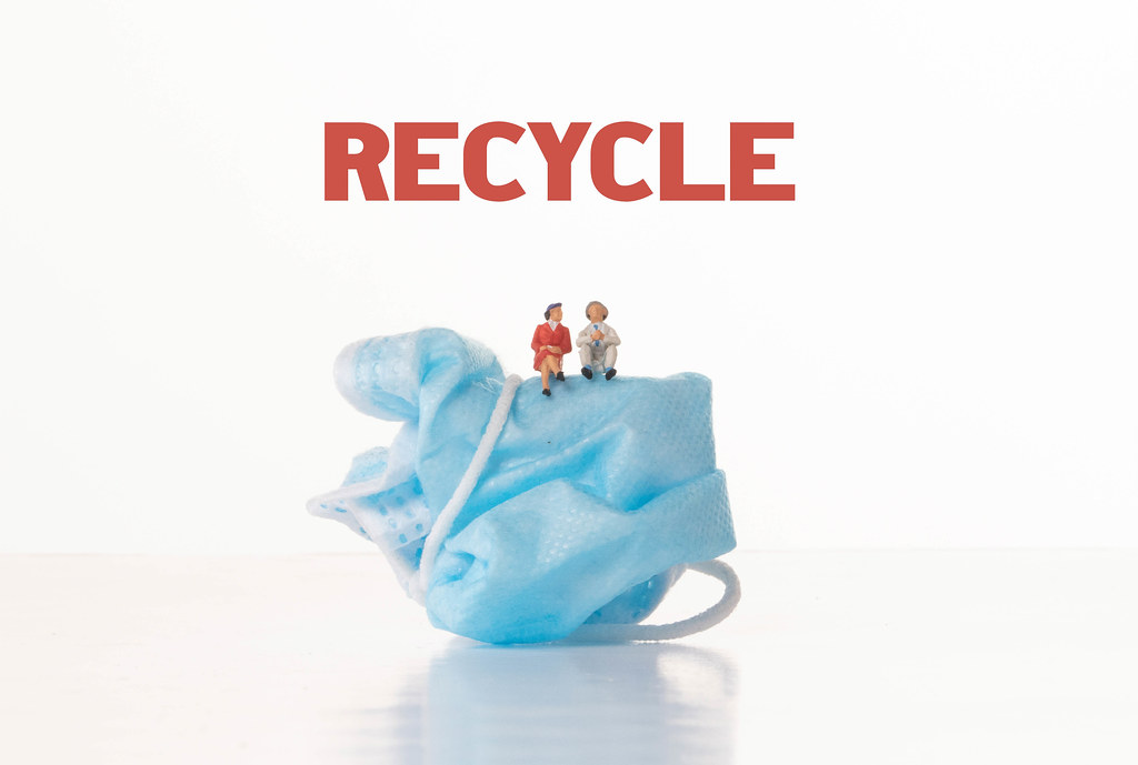 Older man and women sitting on medical face mask with Recycle text