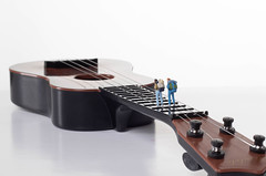 Miniature travelers on a guitar with white background
