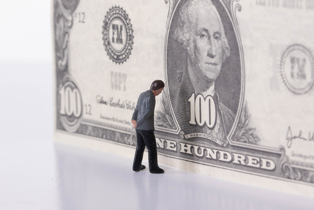 Miniature businessman standing in front of 100 dollar banknote. Paywall concept