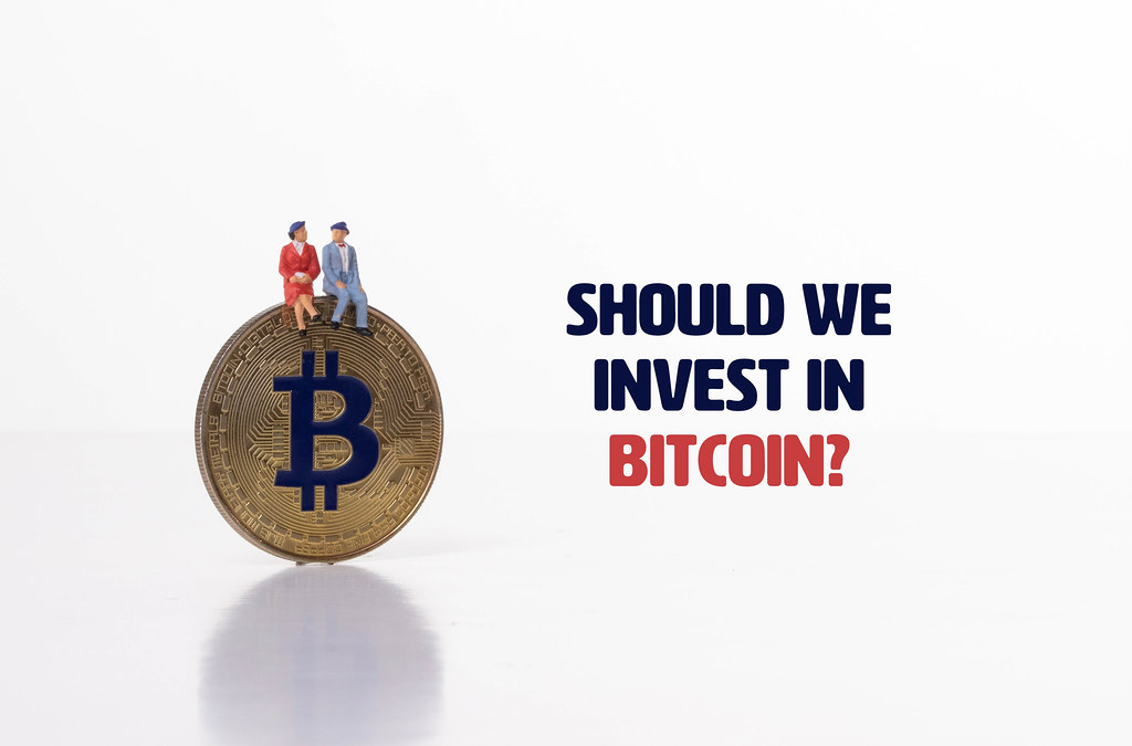 Couple  sitting on Bitcoin coin with Should we invest in Bitcoin text