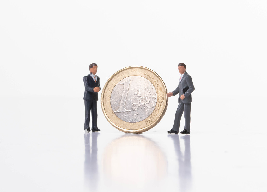 Two businessman with 1 Euro coin on white background