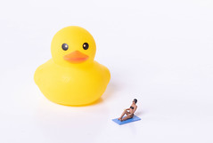 Woman in bathing suit with yellow rubber duck on white background