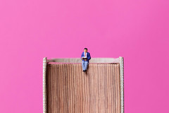 Man sitting on book with pink background