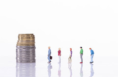 People standing in line in front of coin stack