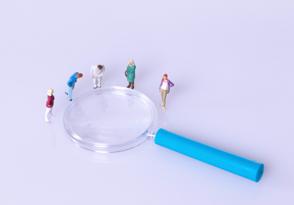 Group of people standing around magnifying glass