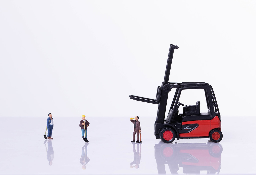 Miniature workers with red forklift on white background