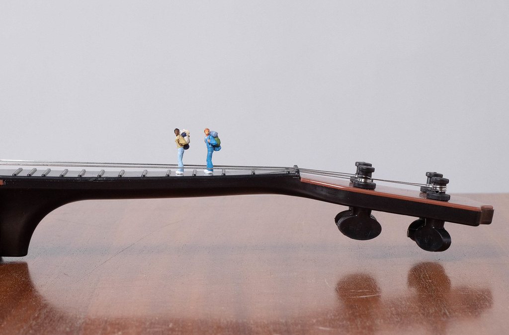 Miniature travelers on a guitar